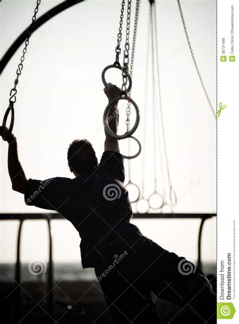 person swinging silhouette of a person swinging on rings royalty free