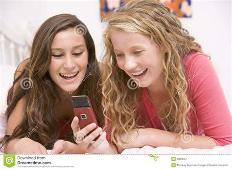 smiling girl using mobile phone in bed royalty free stock teenage girls lying on bed using mobile phone royalty free