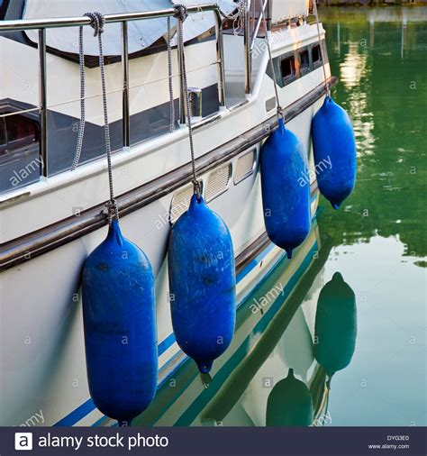 boat fender buoy blue buoys hanging over side of boat used as boat fenders