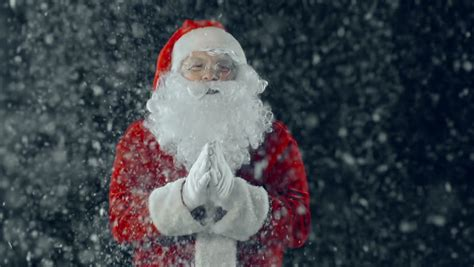 close up of santa claus against black background clapping