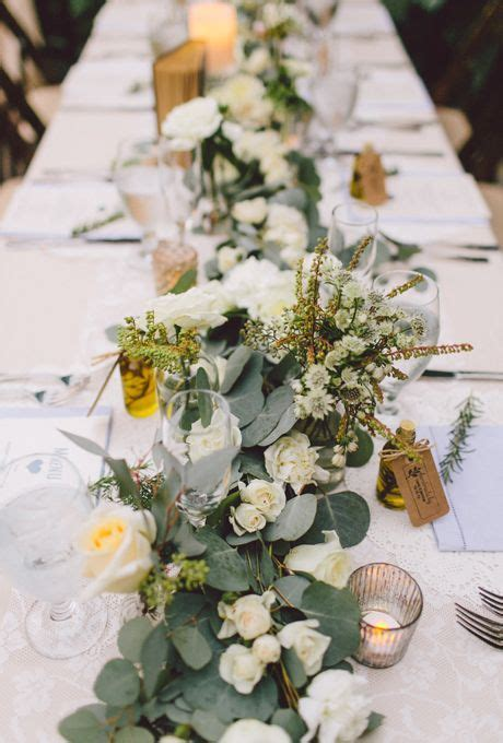 Wedding table with tons of greenery, white roses, and