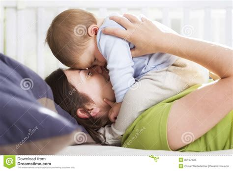 lying down in bed harmonious time mother and son embracing with love and