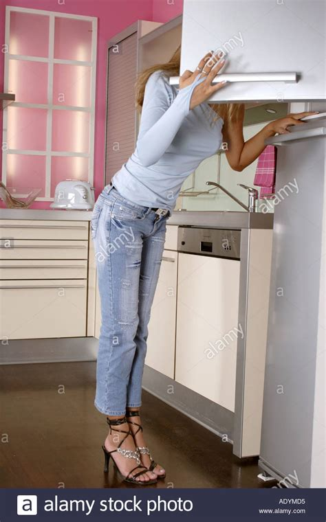 Woman Wearing Jeans And High Heels Leaning Into Opened Stilettos In The Kitchen