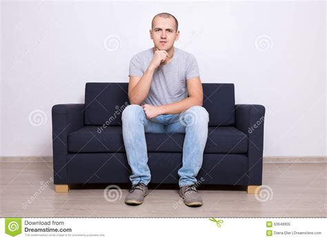 sitting on a sofa handsome man sitting on sofa at home stock photo image