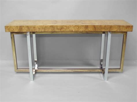 a burled wood console table with a chrome base at