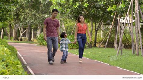 Walking In The happy asian family walking in the park stock footage