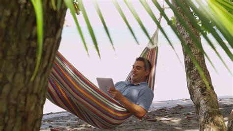 sitting hammock man sitting in hammock using laptop computer costa rica
