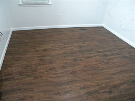brown wooden allure vinyl plank flooring matched with white wall plus white baseboard molding