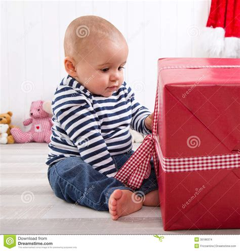 little boys first mundan first christmas baby unwrapping a red present with a red
