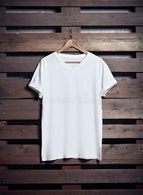 T Shirt Kaos Wood photo of white tshirt hanging on wood background vertical