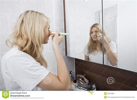 women in bathroom young woman applying blush while looking at mirror in
