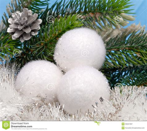 white fluffy new year s balls against a christmas fir tree
