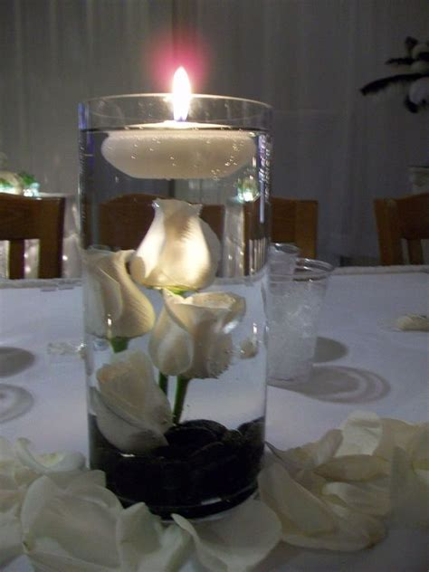 rock centerpieces roses in cylinder vase with black rock for wedding