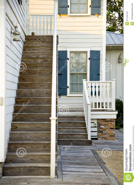 white house with blue shutters white house with blue shutters and wooden stairs stock image image 51724743