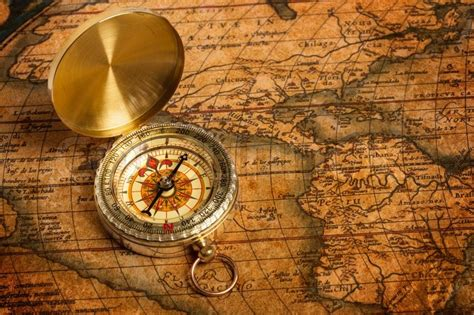 old vintage golden compass on ancient map stock photo