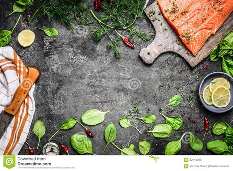 Gourmet Kitchen Designs salmon fish fillets on cutting board and fresh ingredients