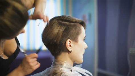 haircuts on women at barbershops female hands of barber comb and cut hair of boy in