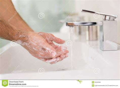 toilet with hand washing washing hands with soap under running water at bathroom
