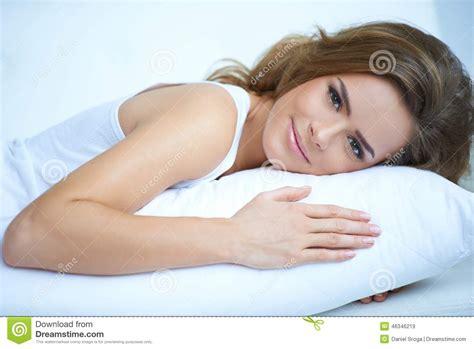 pretty lying prone on white pillow stock photo