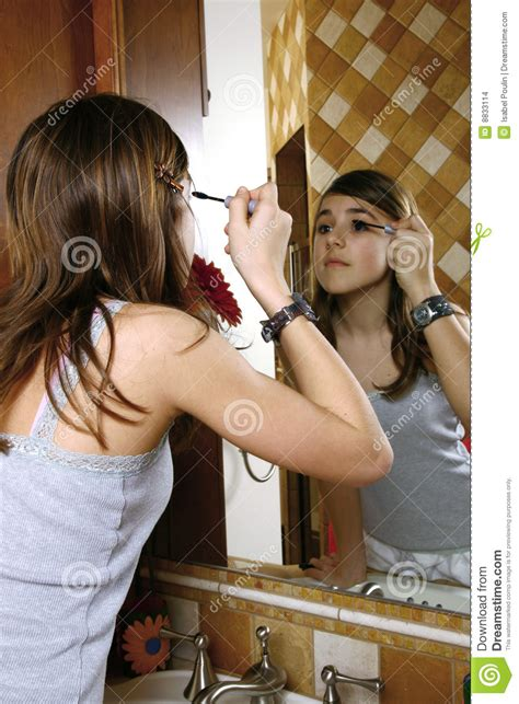 portrait of teenage girl putting lipstick on while looking at her teenage girl with makeup stock photo image of eyeshadow