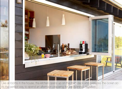 a simple outdoor kitchen that matches the indoor kitchen the windows from the kitchen open out completely to allow