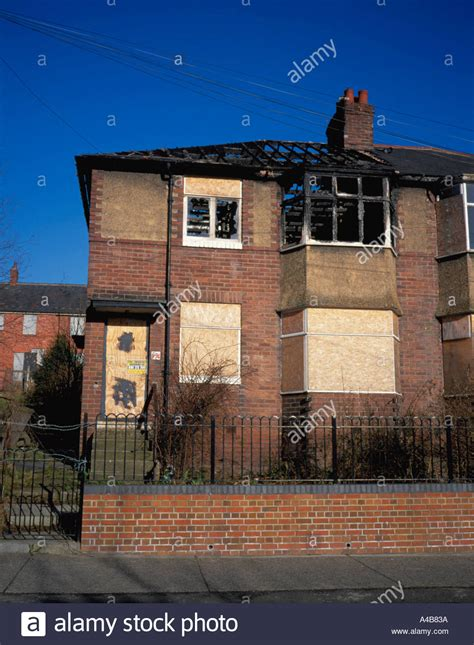 buying a fire damaged house fire damaged house with boarded up windows and doors scotswood stock photo royalty