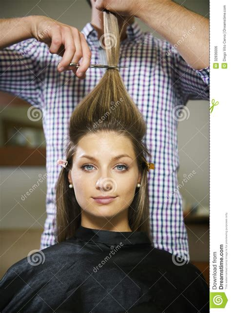 how to cut a womans hair with long crown and tapered back woman in hairdresser shop cutting long hair stock photo