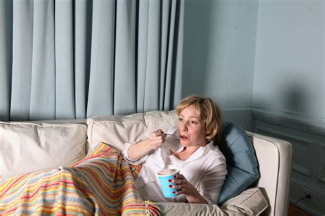 woman eats couch woman eating ice cream on couch watching television stock