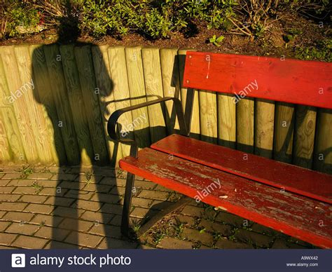 red park bench shadow of a man standing next to a red park bench stock