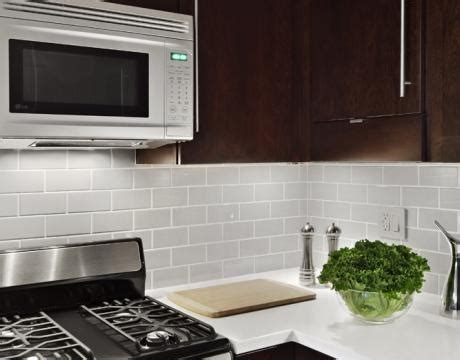 cherry cabinets with gray countertops glass subway tile backsplash with dark cabinets