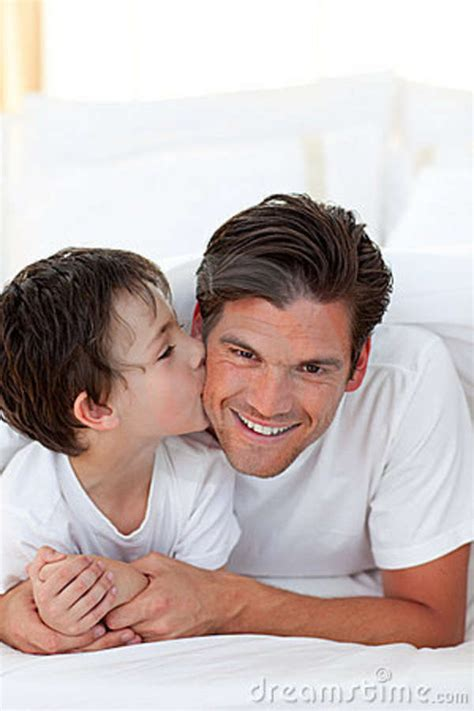 boy kissing a girl in bedroom little boy kissing his father lying on bed stock photo