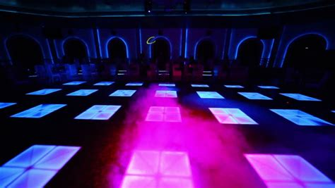 table dance near people sit at tables near dance floor with color light and
