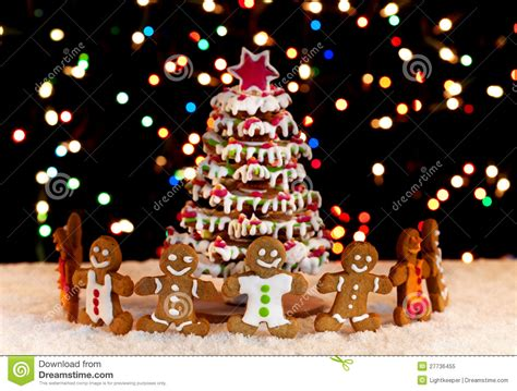 happy gingerbread people around the christmas tree stock