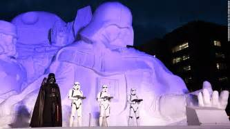 Darth vader leads a posse of stormtroopers with icy lightsaber in hand