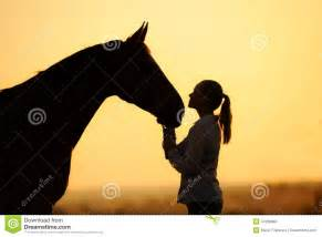 Cowboy Wall Murals silhouette of girl with horse at the sunset stock photo