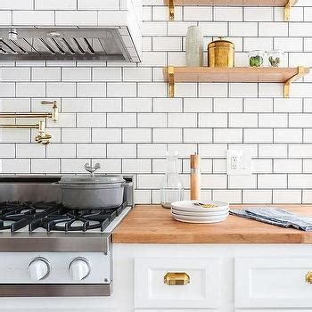 stacked wood kitchen shelves with iron brackets white kitchen cabinets with brass cup pulls and butcher