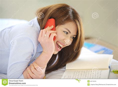 smiling girl using mobile phone in bed royalty free stock beautiful asian teen lay down smile with mobile ph stock