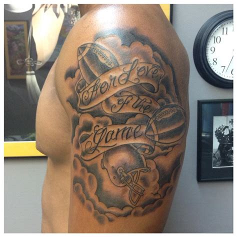 black ink football with banner tattoo on man left shoulder