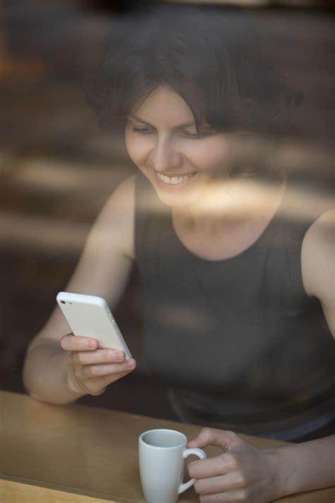 imagenes graciosas tomando cafe mujer tomando caf 233 y sonriendo mientras mira el m 243 vil
