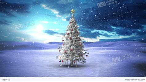 snow falling christmas tree in snowy landscape stock