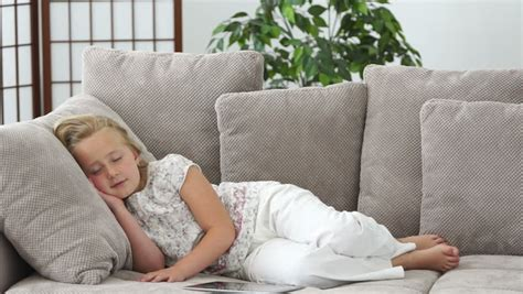 little couch little girl resting on a couch and smiling stock footage