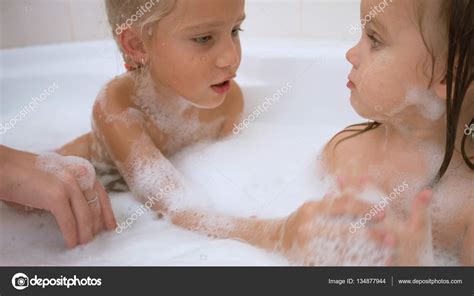 two girls in a bathtub two cute little sisters bathing in the bath stock photo