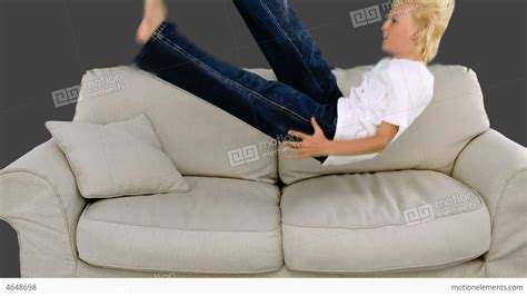 no jumping on the couch young boy jumping on the sofa on grey background stock