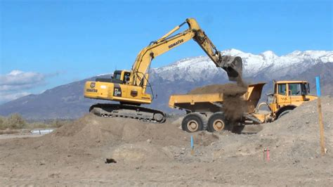 Machine Truck Construction Limited komatsu pc220lc excavator loading an articulated volvo dump truck on a dusty construction site