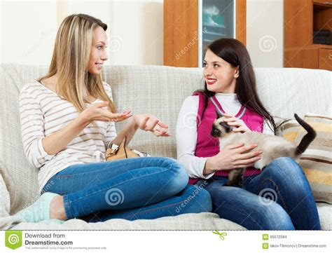 two girls having on couch two girls sitting on sofa and gossiping stock photo