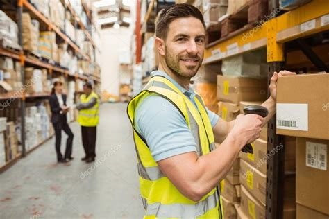 warehouse worker scanning box while smiling at