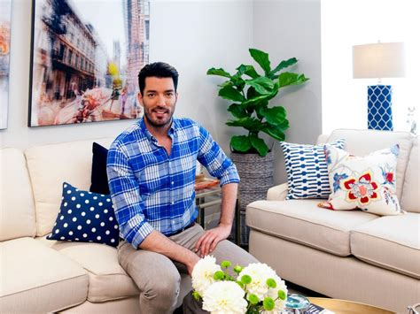 drew and scott pose in renovated living room hosts drew property brothers drew and jonathan scott on hgtv s buying