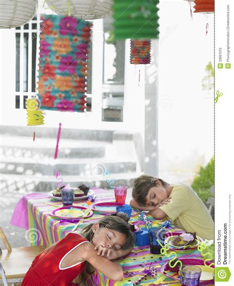 themes girl x2 kids sleeping at table after birthday party stock photo