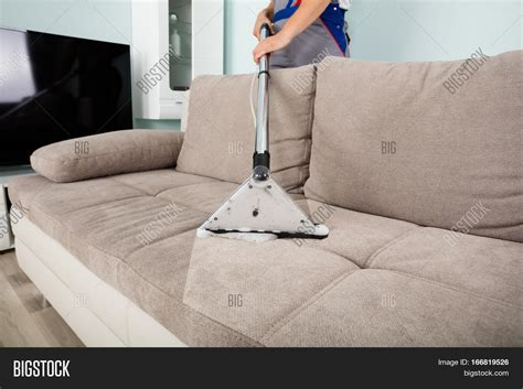 vacuum sofa young male worker cleaning sofa with vacuum cleaner stock