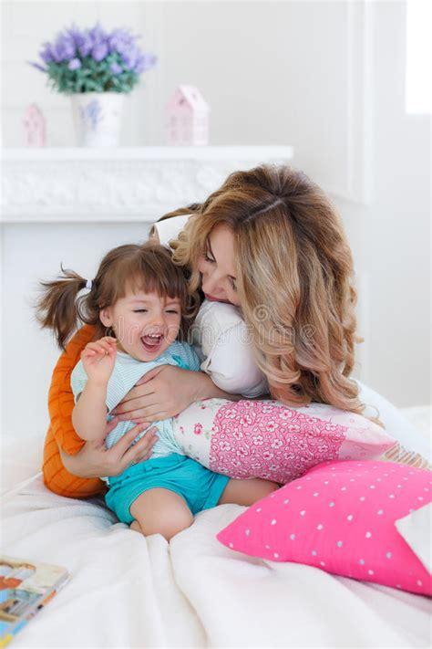 giochi sul letto giovane madre felice gioca con sua figlia sul letto a